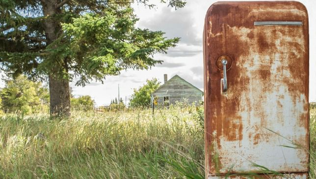 rusted refrigerator sitting outside