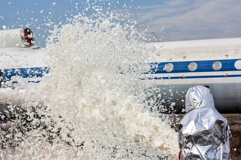 Firefighting foam being sprayed at an airplane