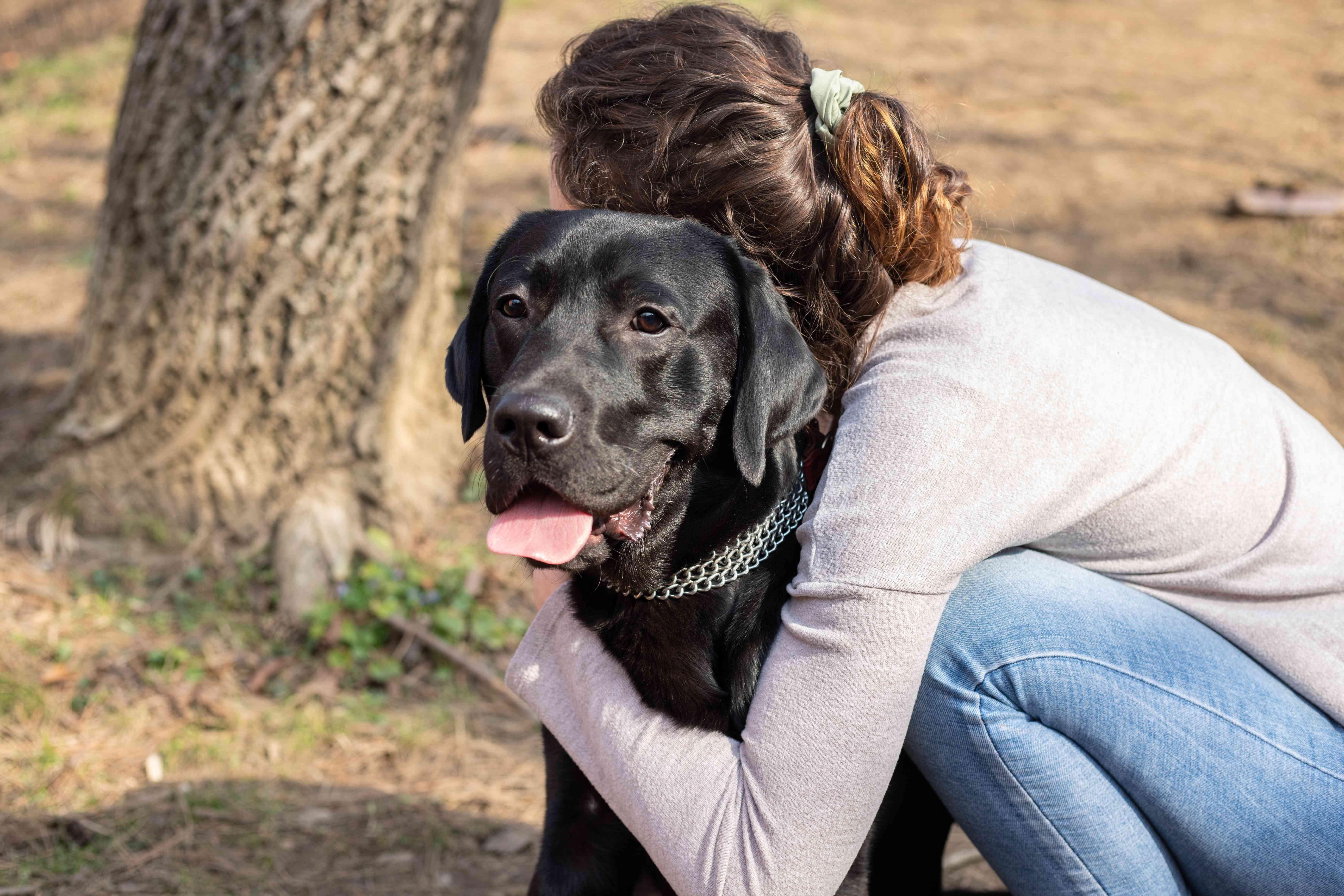 woman hugs black dog outside near a tree