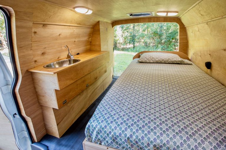 Back of a renovated van with a bed on one side an a sink and counter on the other