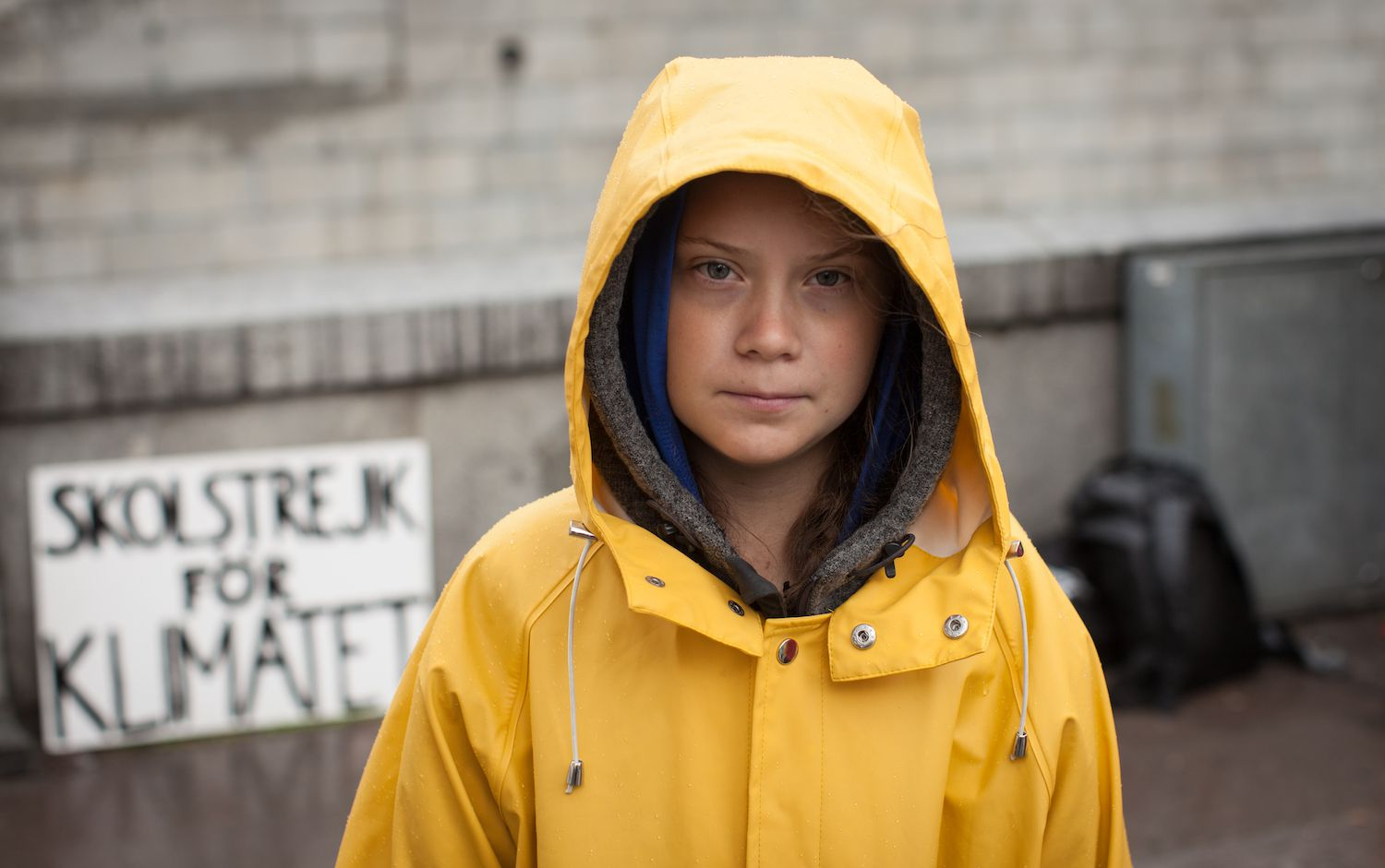 Young child in a yellow rain slicker staring at camera