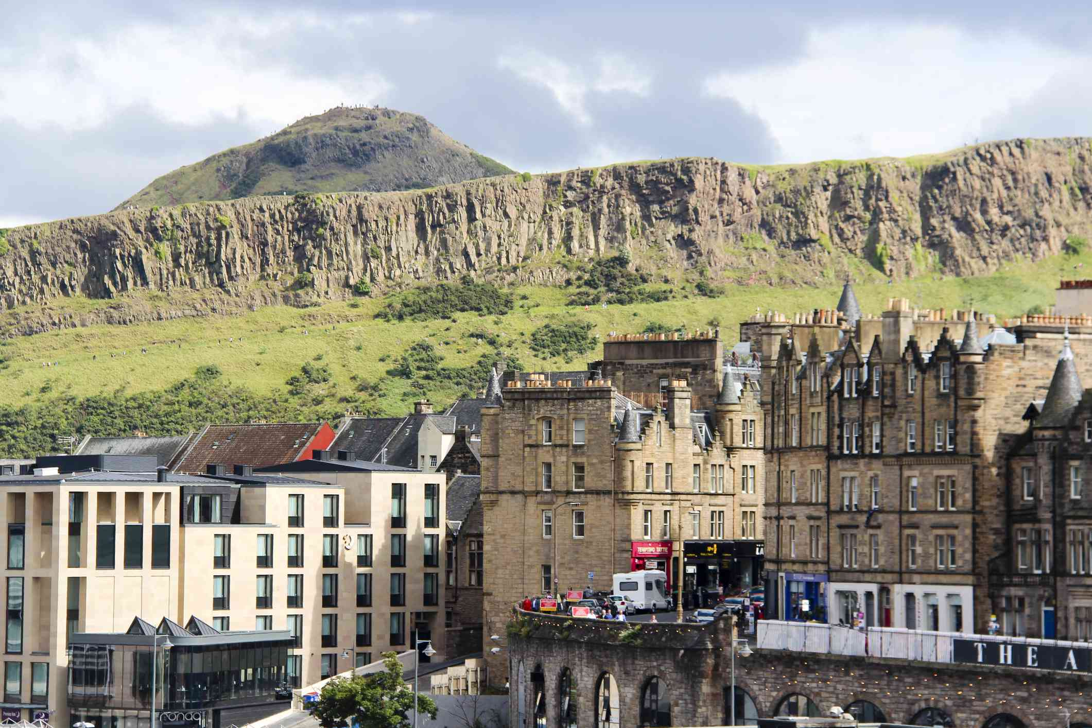 View of Arthur's Seat, a mountain in the city of Edinburgh, Scotland behind smaller hills and grass covered field with multi-story buildings of the city in the foreground