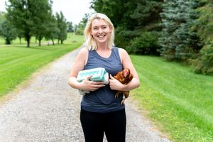 woman smiles while holding egg carton and chicken