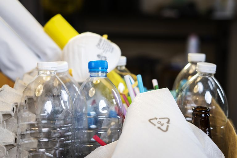Plastic bottles and garbage in a box, one piece showing a recycling symbol.