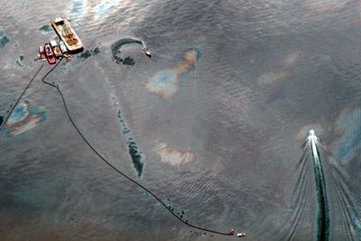Aerial view of oil-covered water being skimmed by small boat following Exxon Valdez oil spill