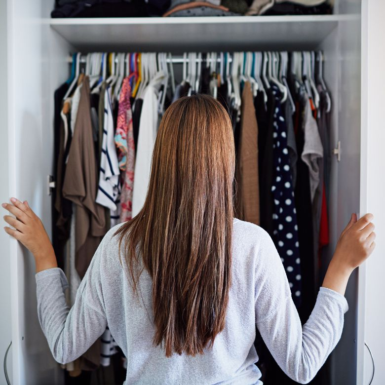 a woman looking at her clothes on hangers