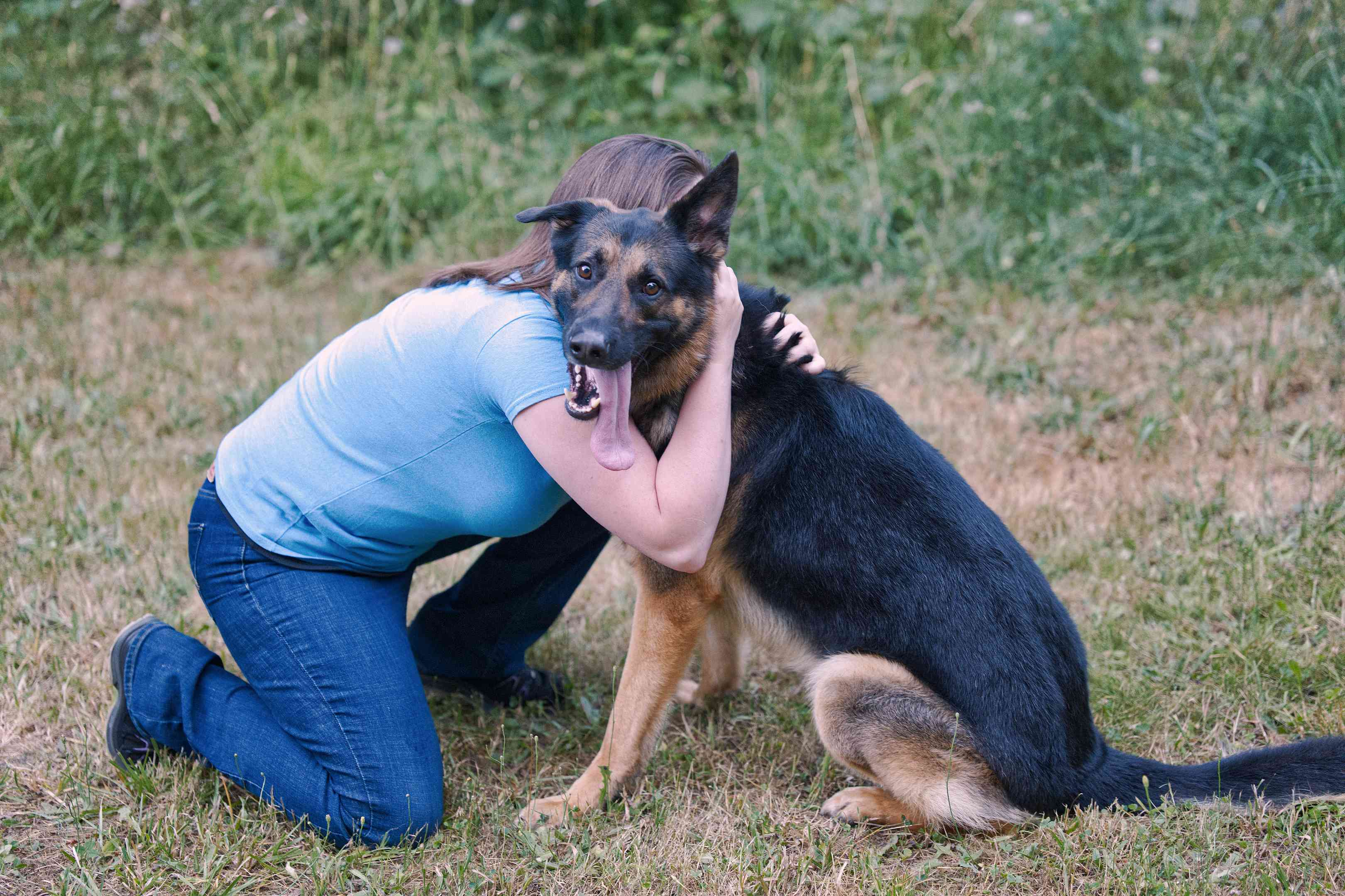 woman bends down to ground outside to hug German Shepherd dog with tongue out
