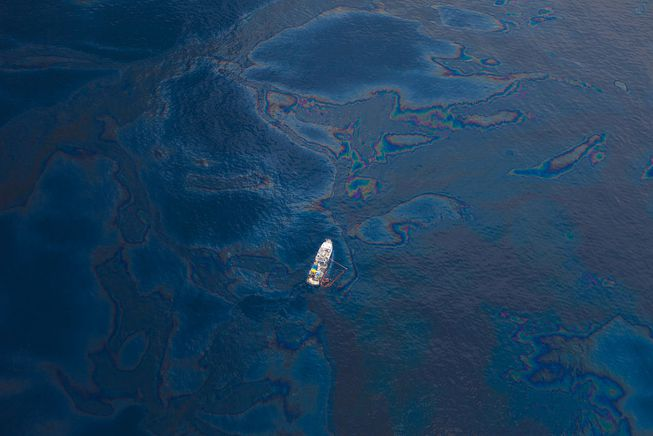 A boat sails through an oil slick caused by the Deepwater Horizon oil spill