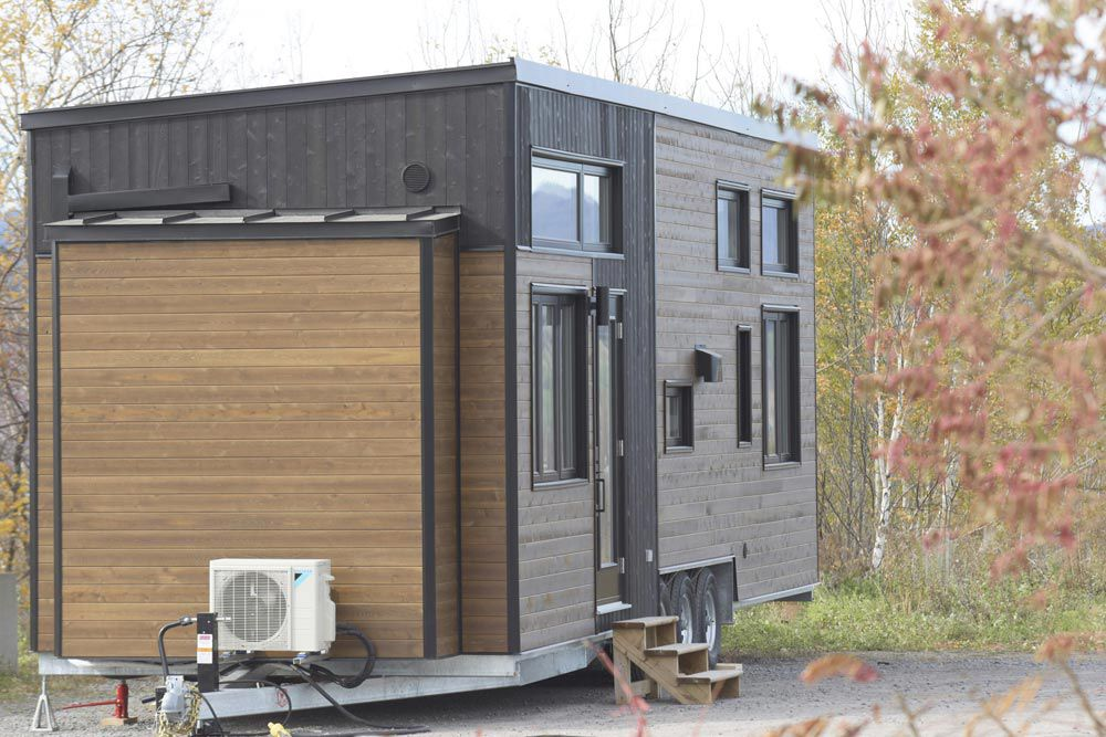 Rear/side view of tiny home elevated on a trailer
