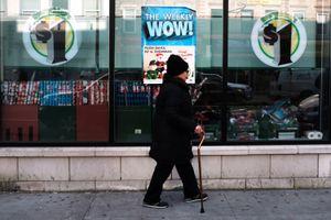 Woman walking past dollar store.