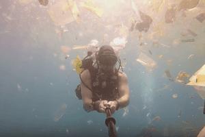 Diver filming plastic floating off Penida Island