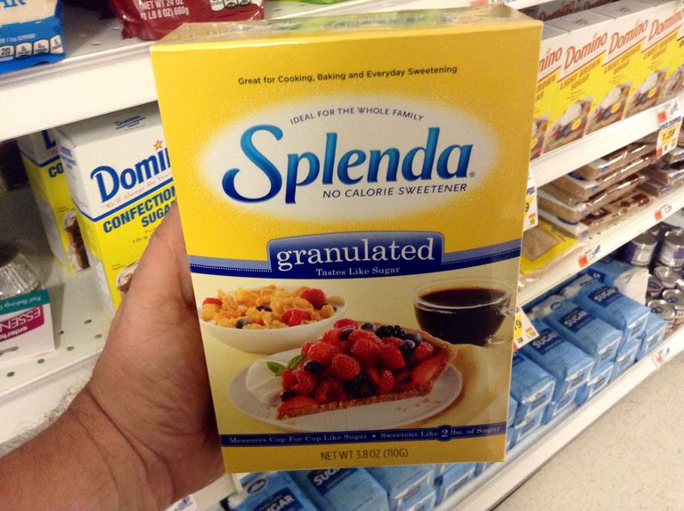 Hand holding box of Splenda in the sugar aisle of a grocery store