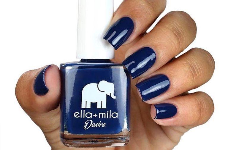 A woman holding up blue nail polish.