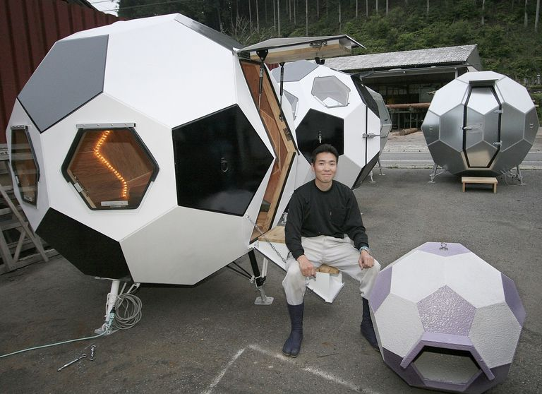 A man sits by soccer ball shaped emergency housing in Japan.