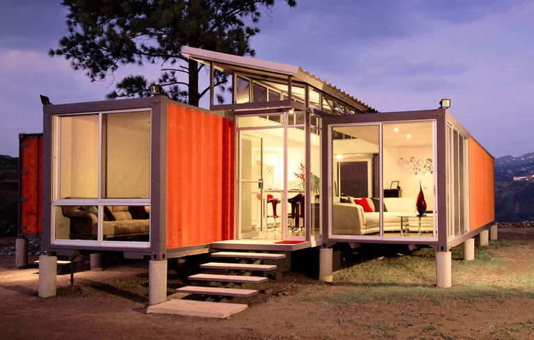 An orange container box house against a purple evening sky.