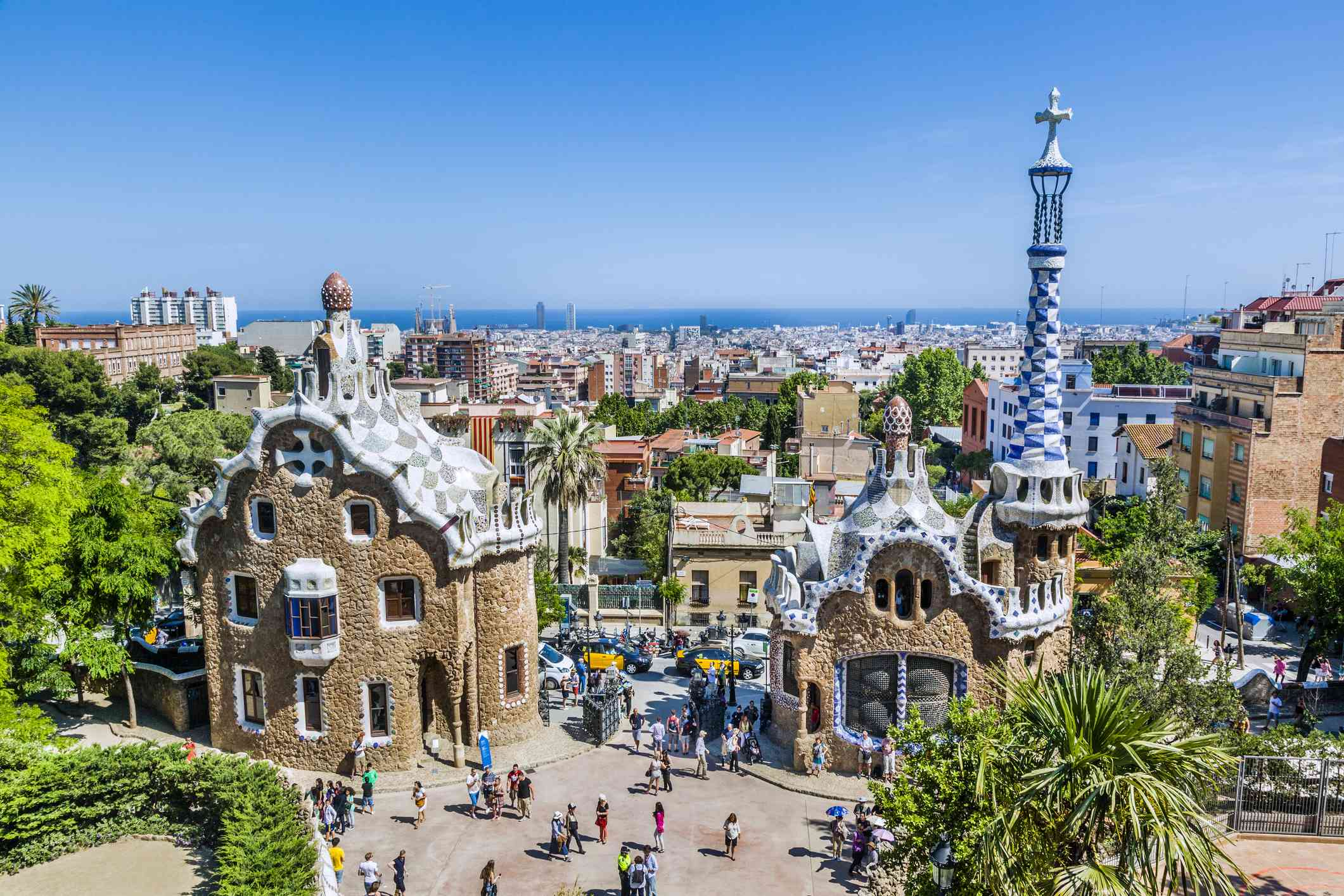 The colorful and whimsical buildings and manicured trees of Parc Güell with the ocean in the distance and a clear, blue sky above