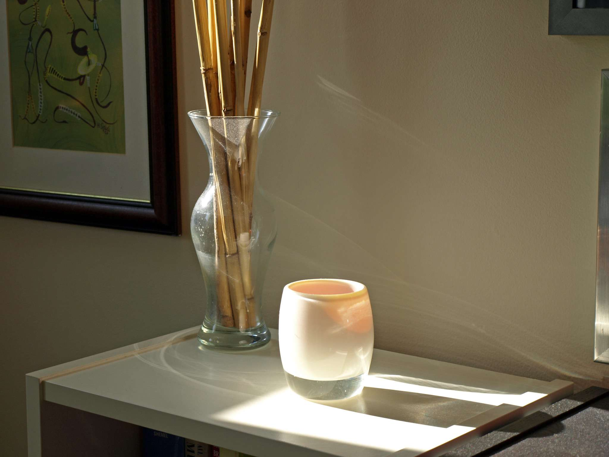 Glassy baby votive sitting on top of a bookshelf next to a vase of dried bamboo