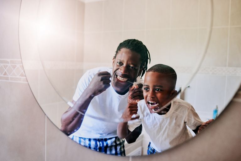 father and son flossing in the mirror