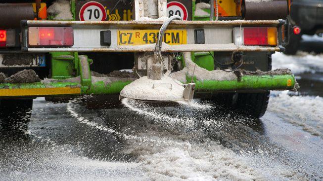 A salt truck applies salt to an icy road