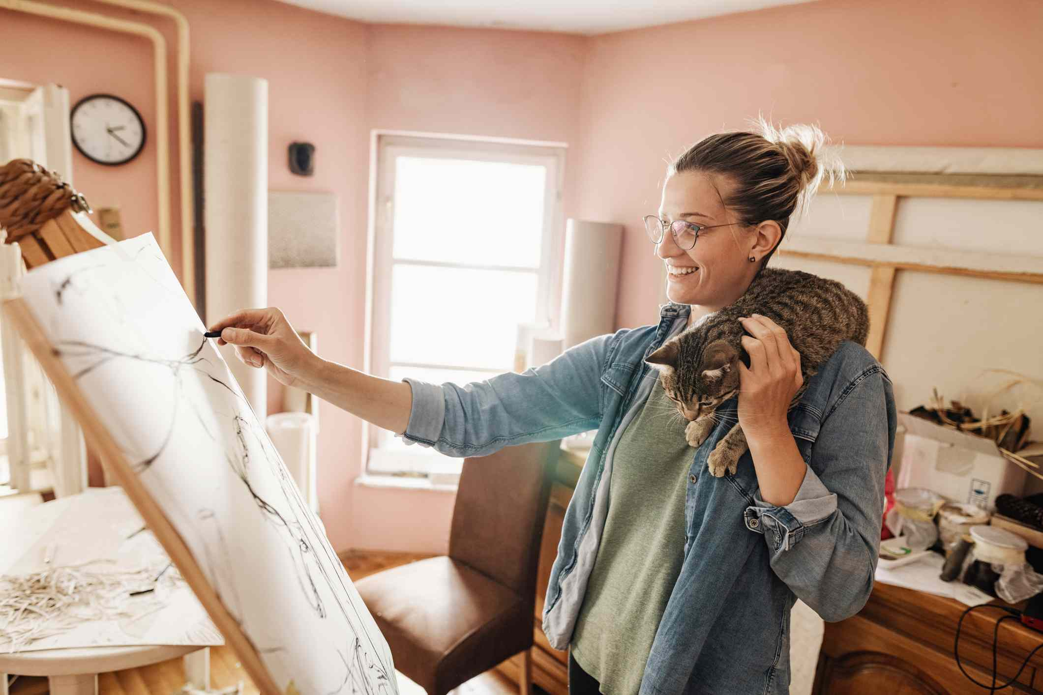 tabby cat crawls on woman's shoulder as she draws on canvas
