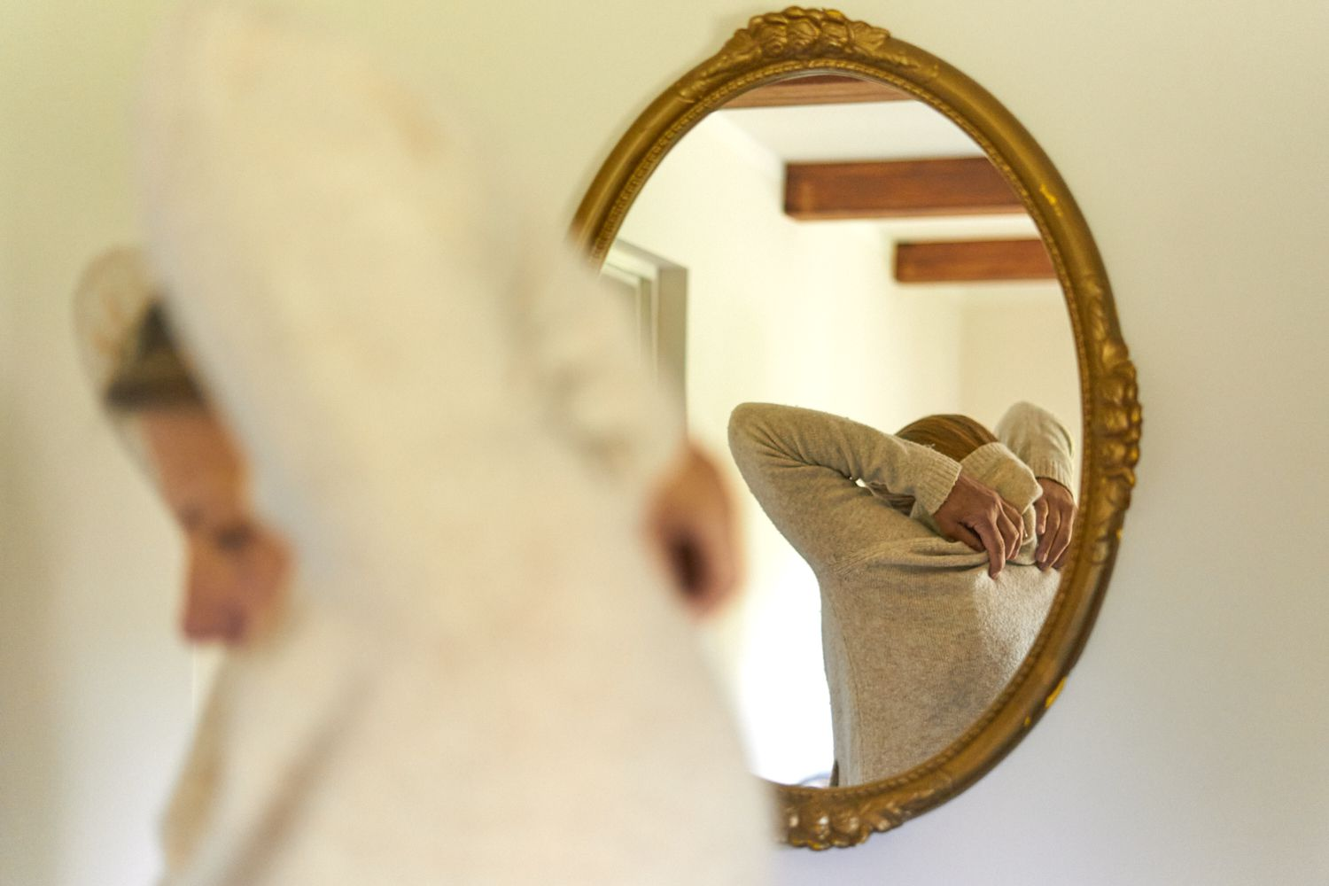 reflection of person in gold oval mirror removing cream-colored sweater