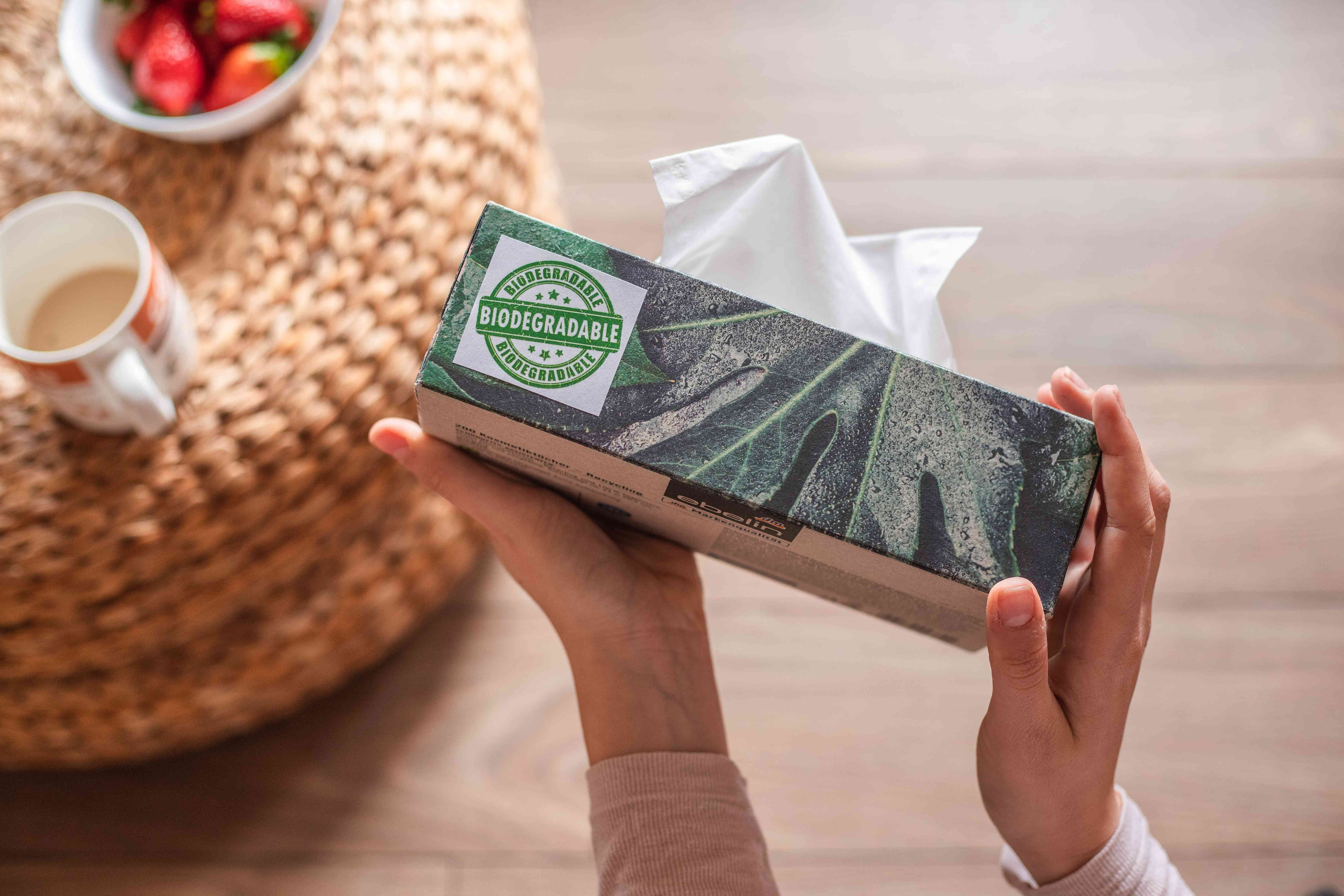 person's hands hold tissue box over table with biodegradable label on the side