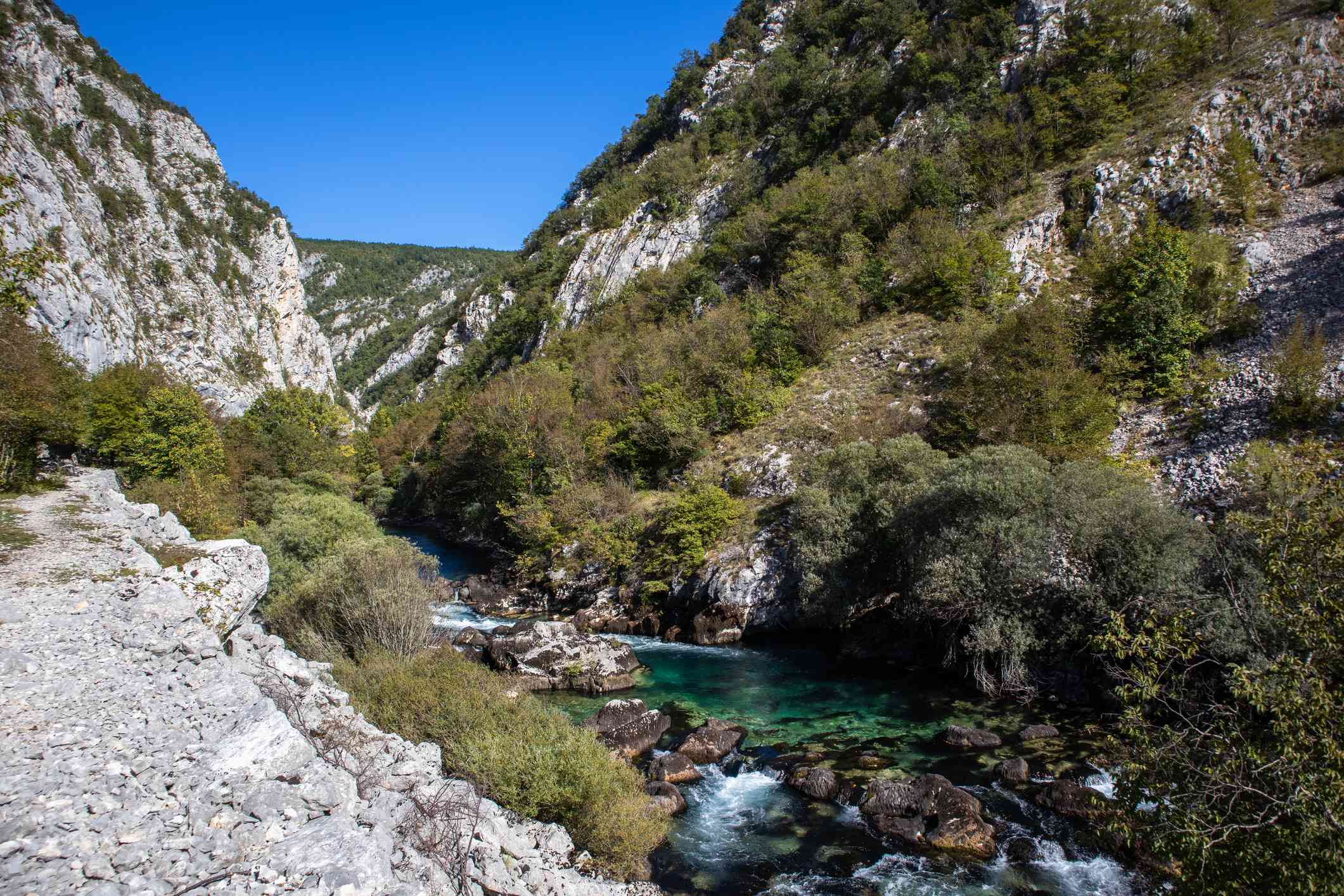 A turquoise colored river flows through rocky shrubland