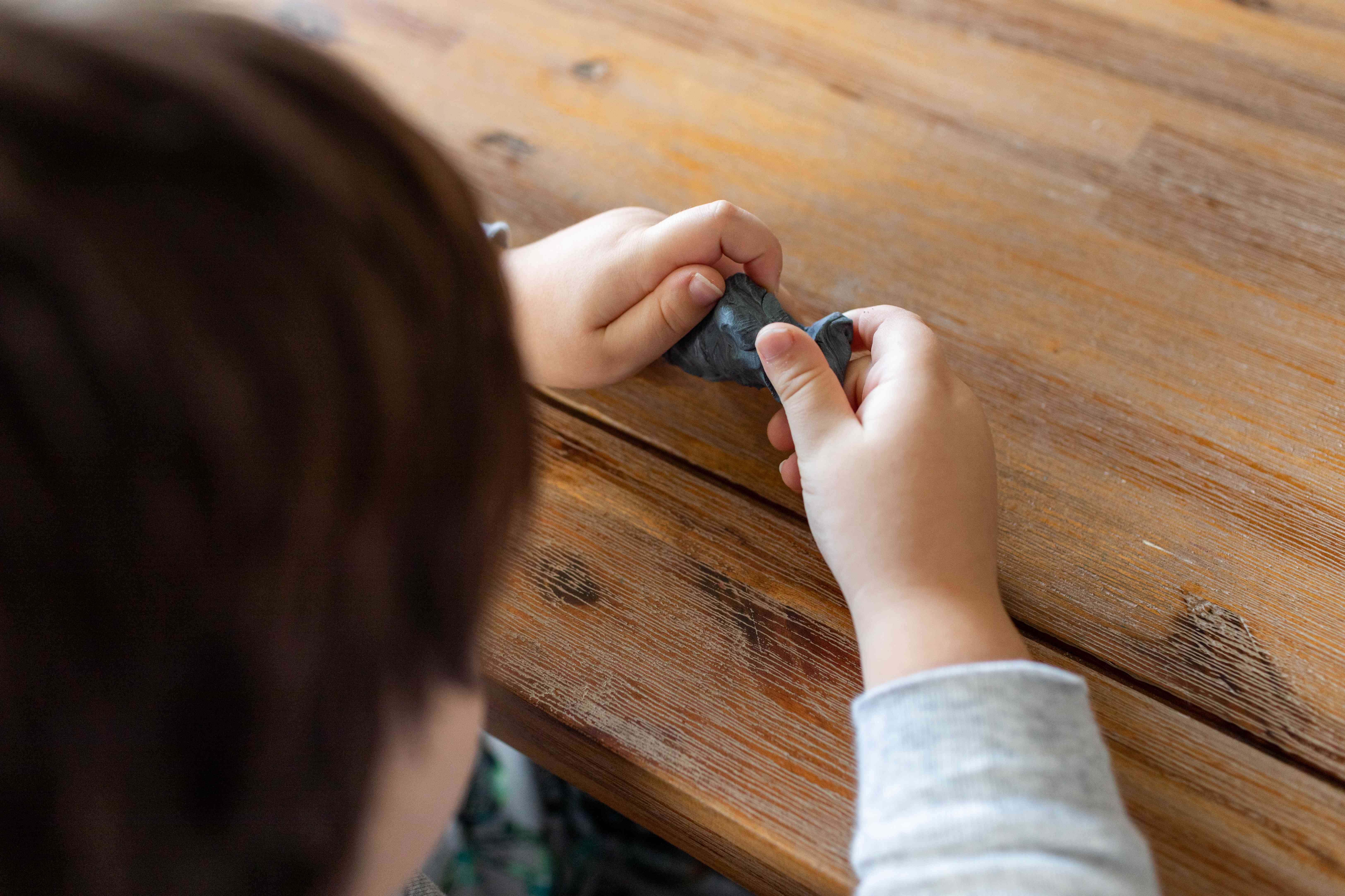 little kid plays with homemade gray dryer lint clay on wooden table