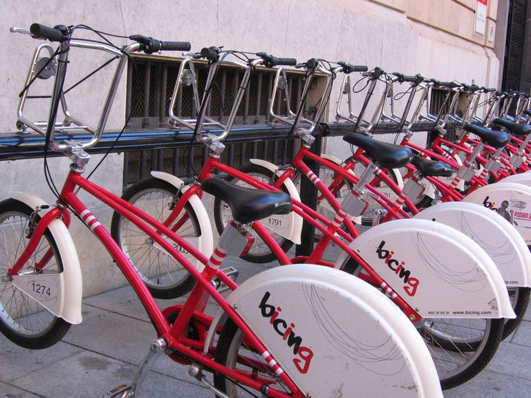 Red Bicing bikes parked on a rack in Barcelona.
