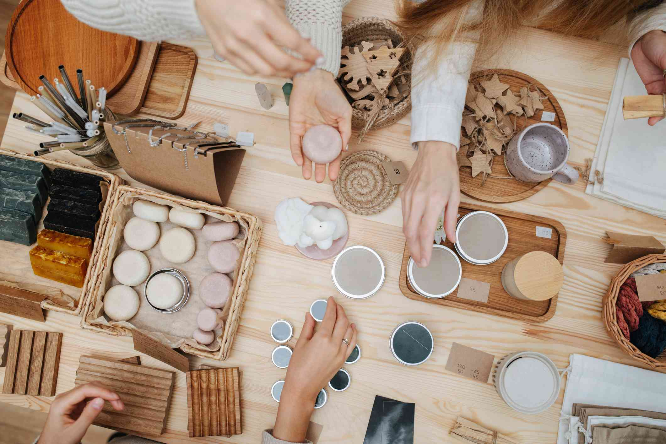 Aerial view of women looking at eco cosmetics in recyclable packaging.