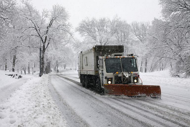 Snowplow truck clearing a snow-covered street