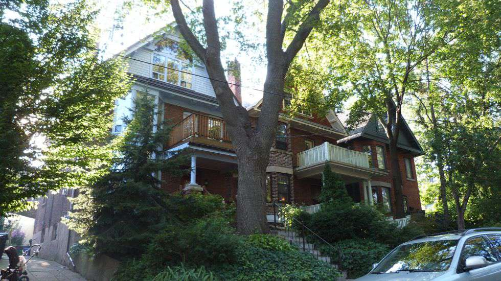 Street view of a multi-story brown house, with a large tree and greenery in front