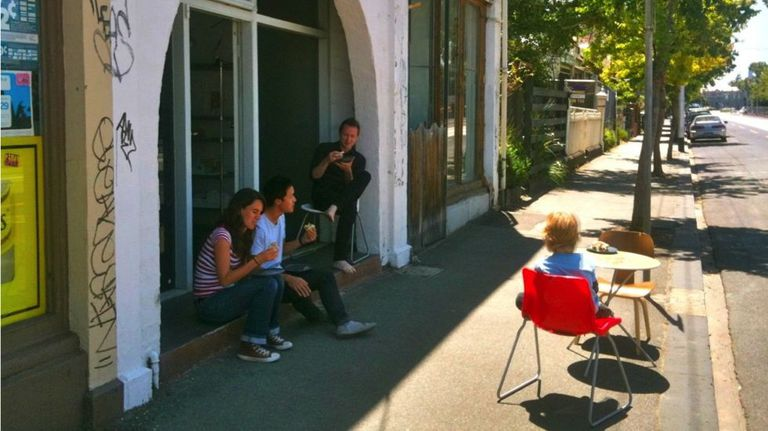 Street scene showing people sitting in the shade