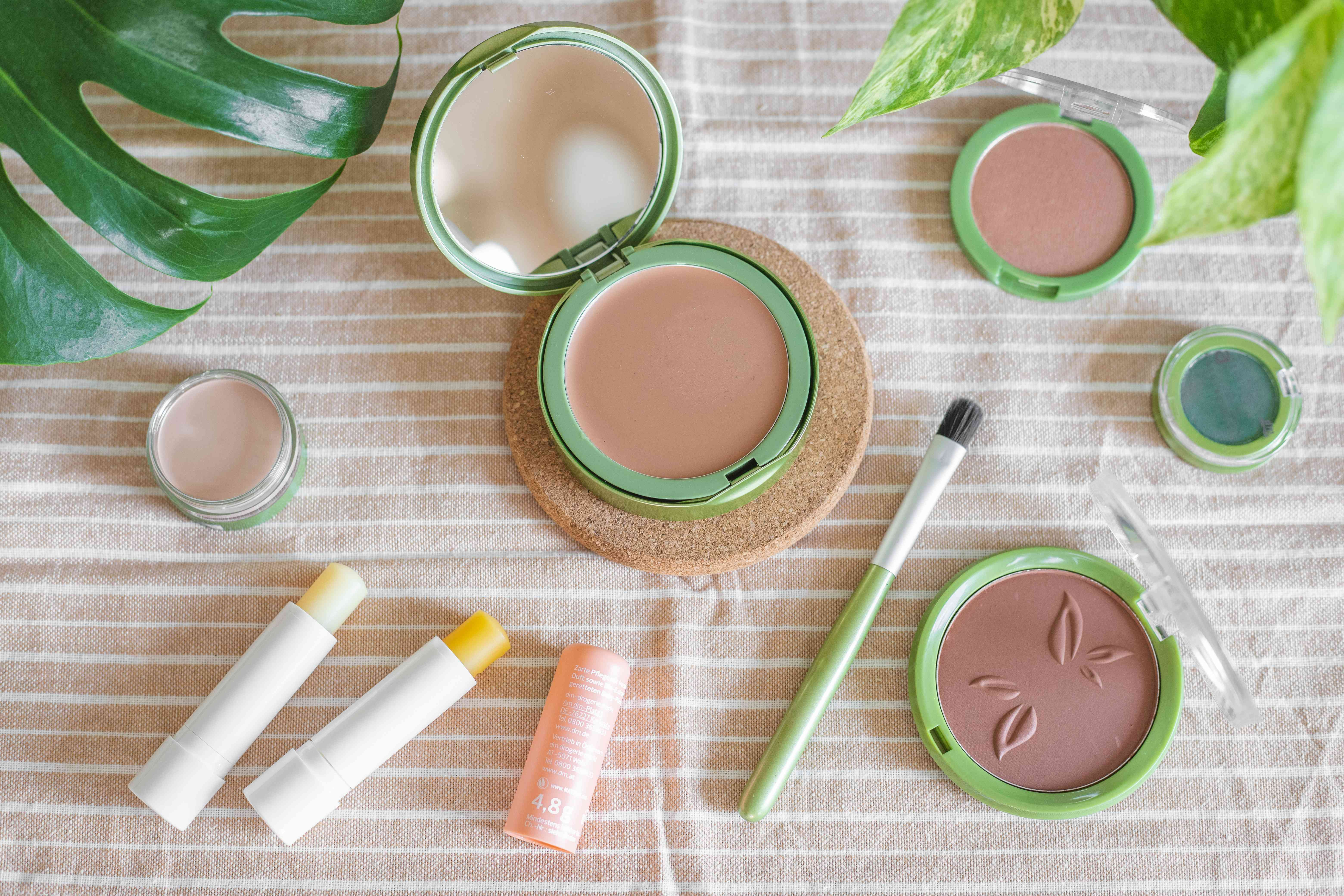 flat lay of rosy hues of waterless makeup cream blushes and lipstick