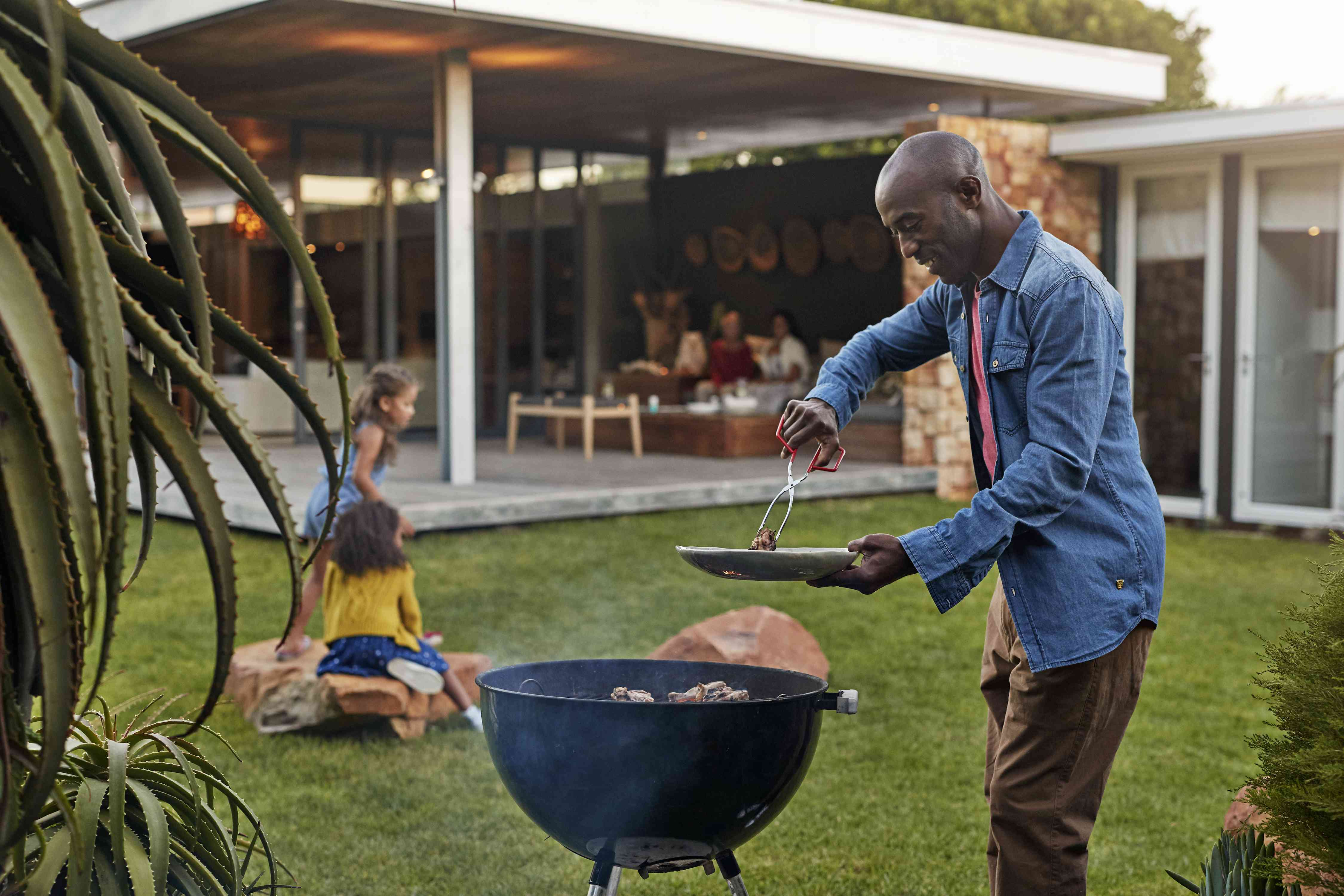 A man in a denim shirt grills while a family plays in the background