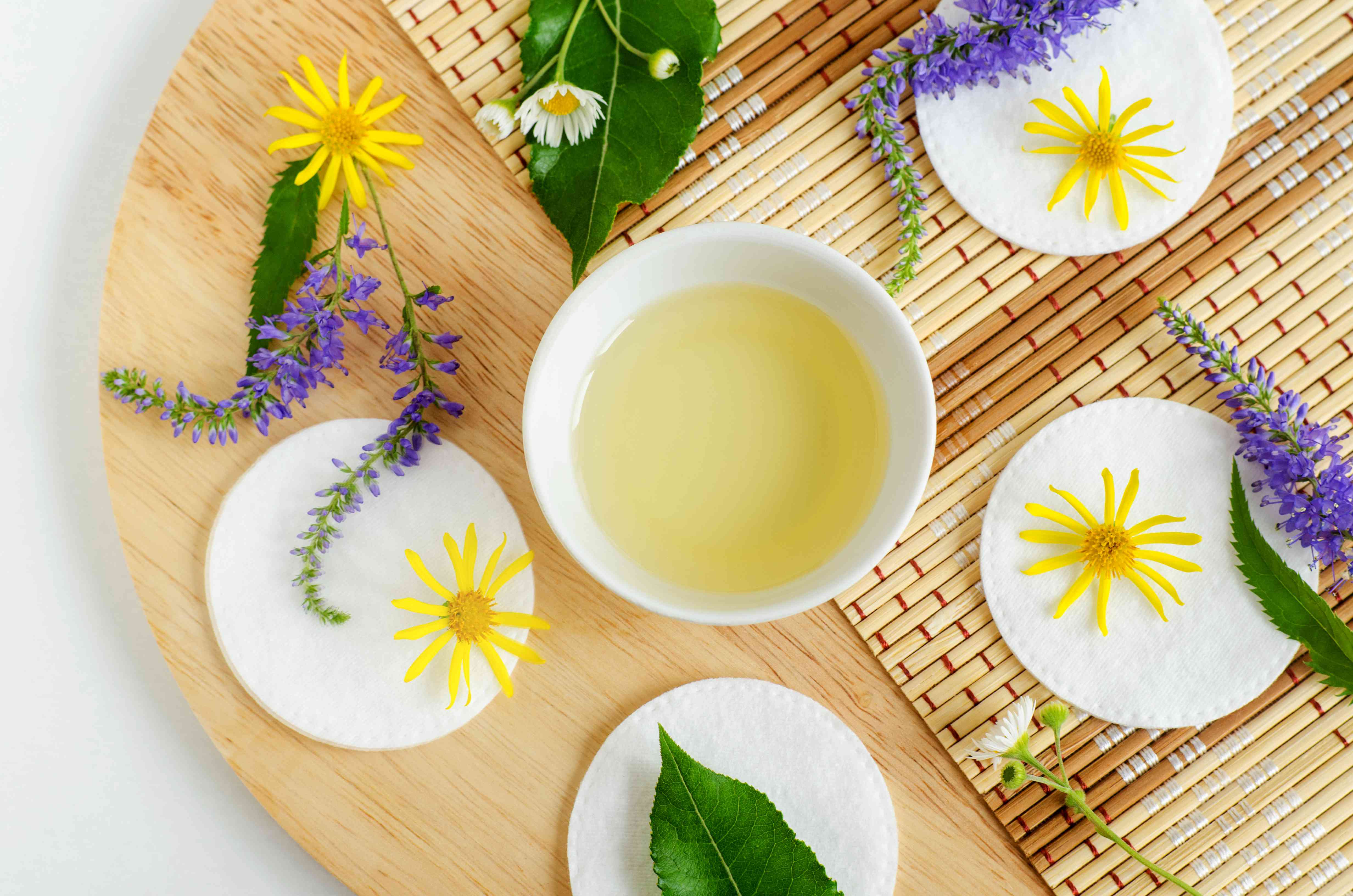 Small white bowl with cosmetic (massage, cleansing) aroma oil, cotton pads and wild flowers. Natural skin care, homemade spa and beauty treatment recipe. Top view, copy space.