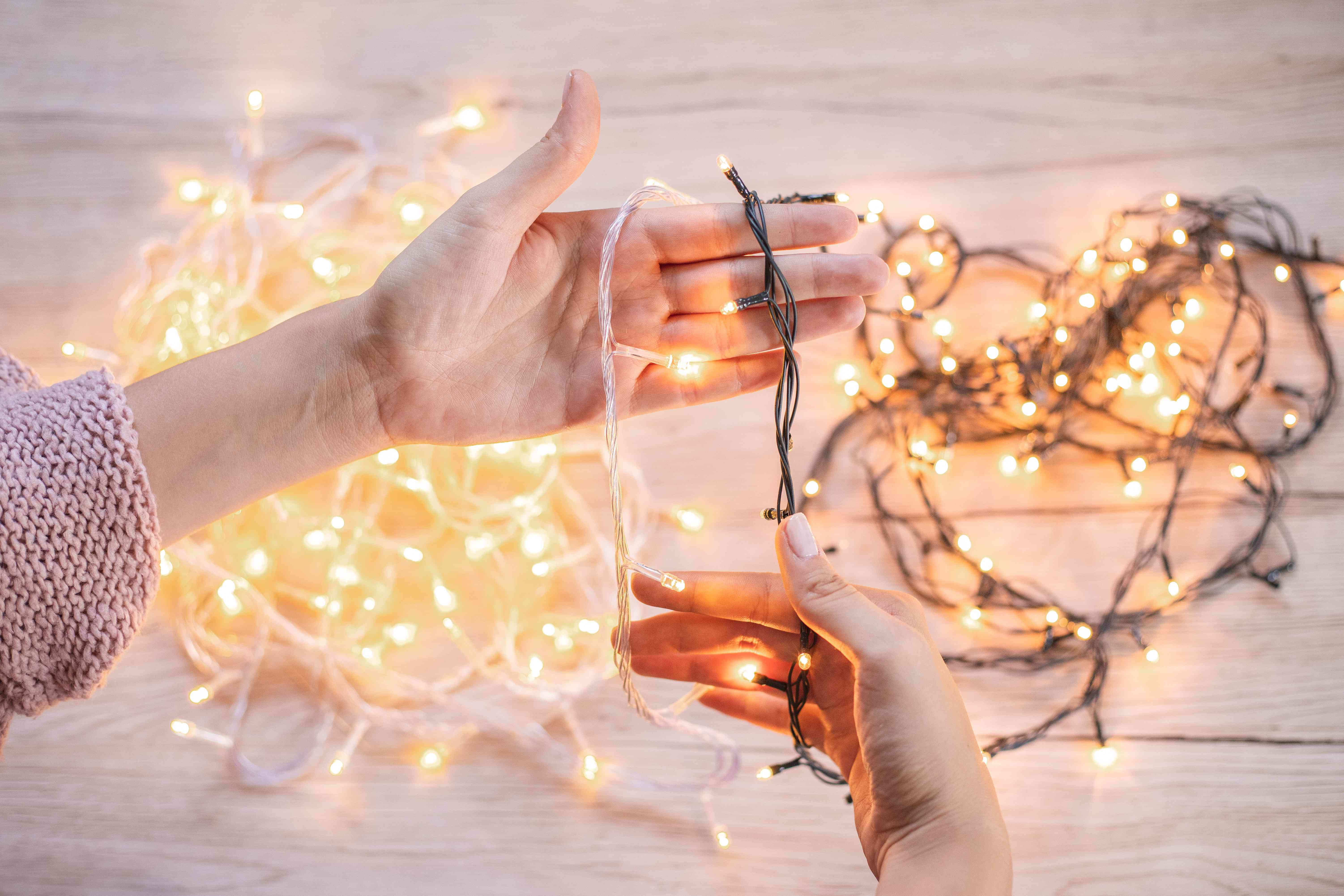 hands compare different bundles of glowing LED Christmas lights