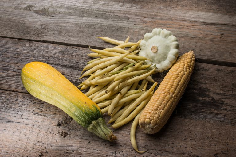 Yellow squash, corn and wax beans on a wooden tabletop