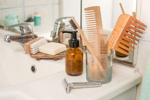 Zero waste products on a bathroom counter including bamboo combs, a metal razor, bamboo toothbrush, bar of soap, and more