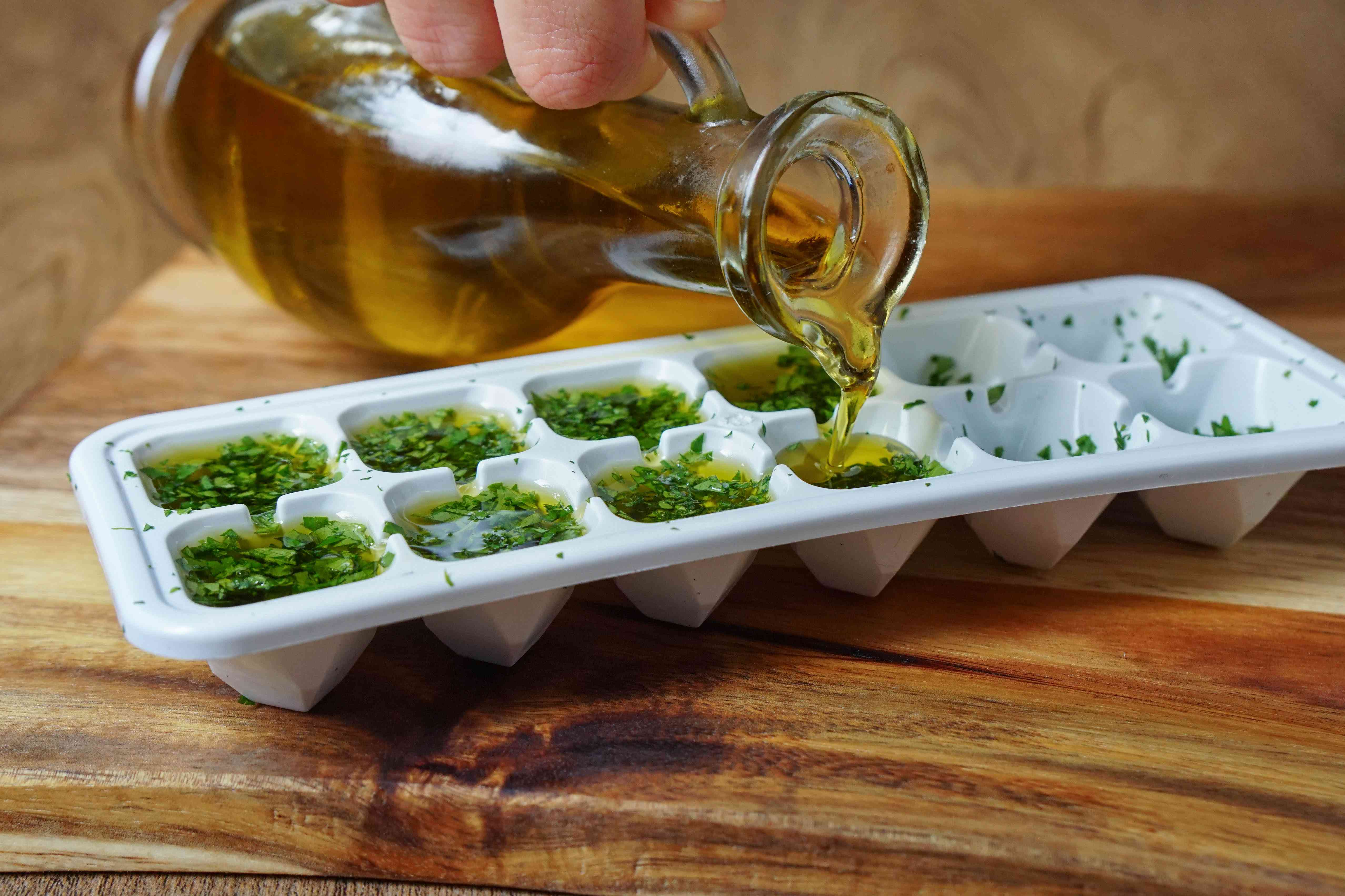 olive oil is poured from glass decanter into ice cube tray filled with chopped parsley to preserve