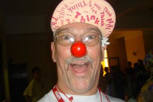 Patch Adams smiling and wearing a hat and red clown nose