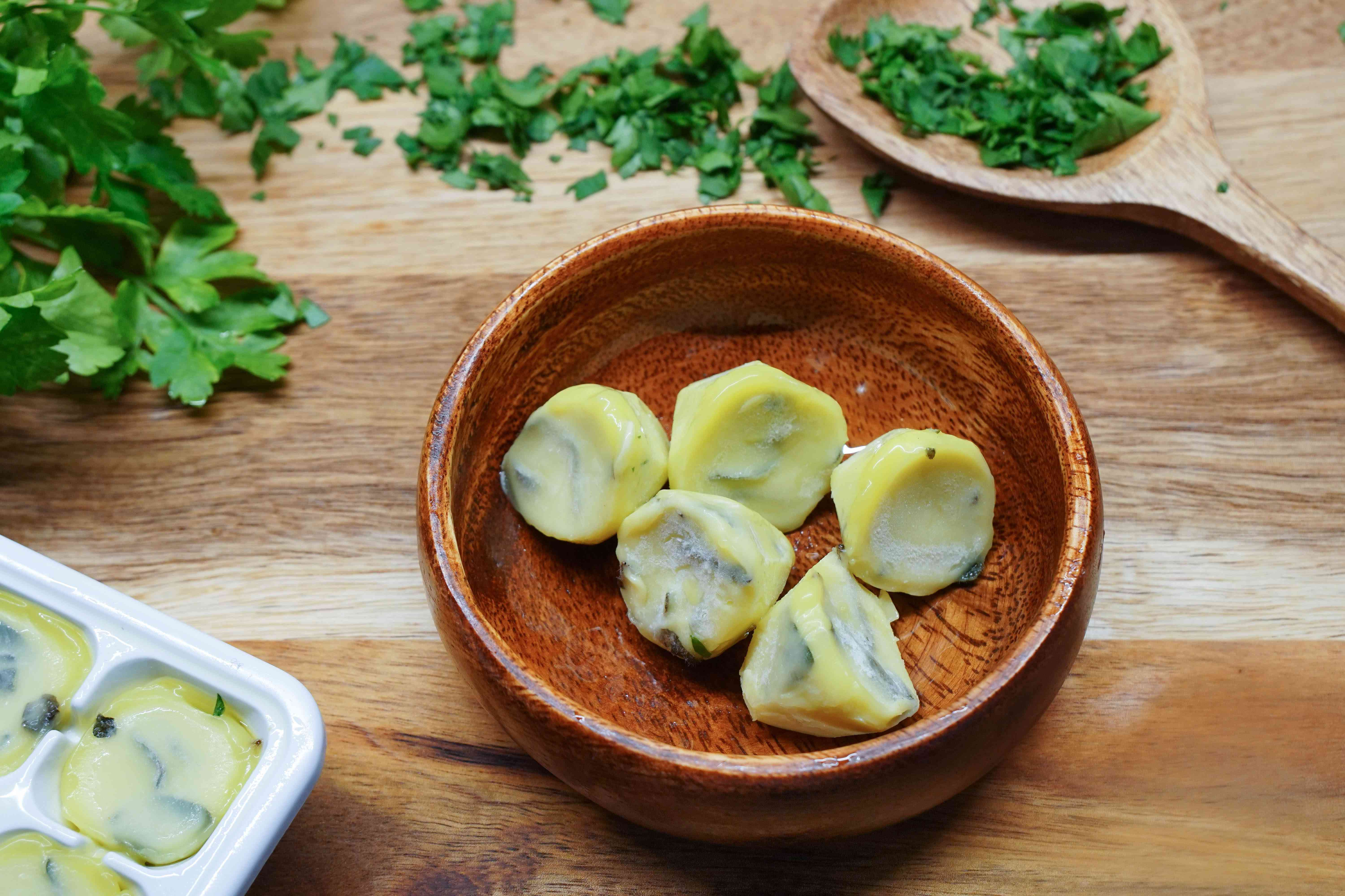 frozen ice cubes of butter and fresh parsley sit in wooden bowl with parsley scattered nearby