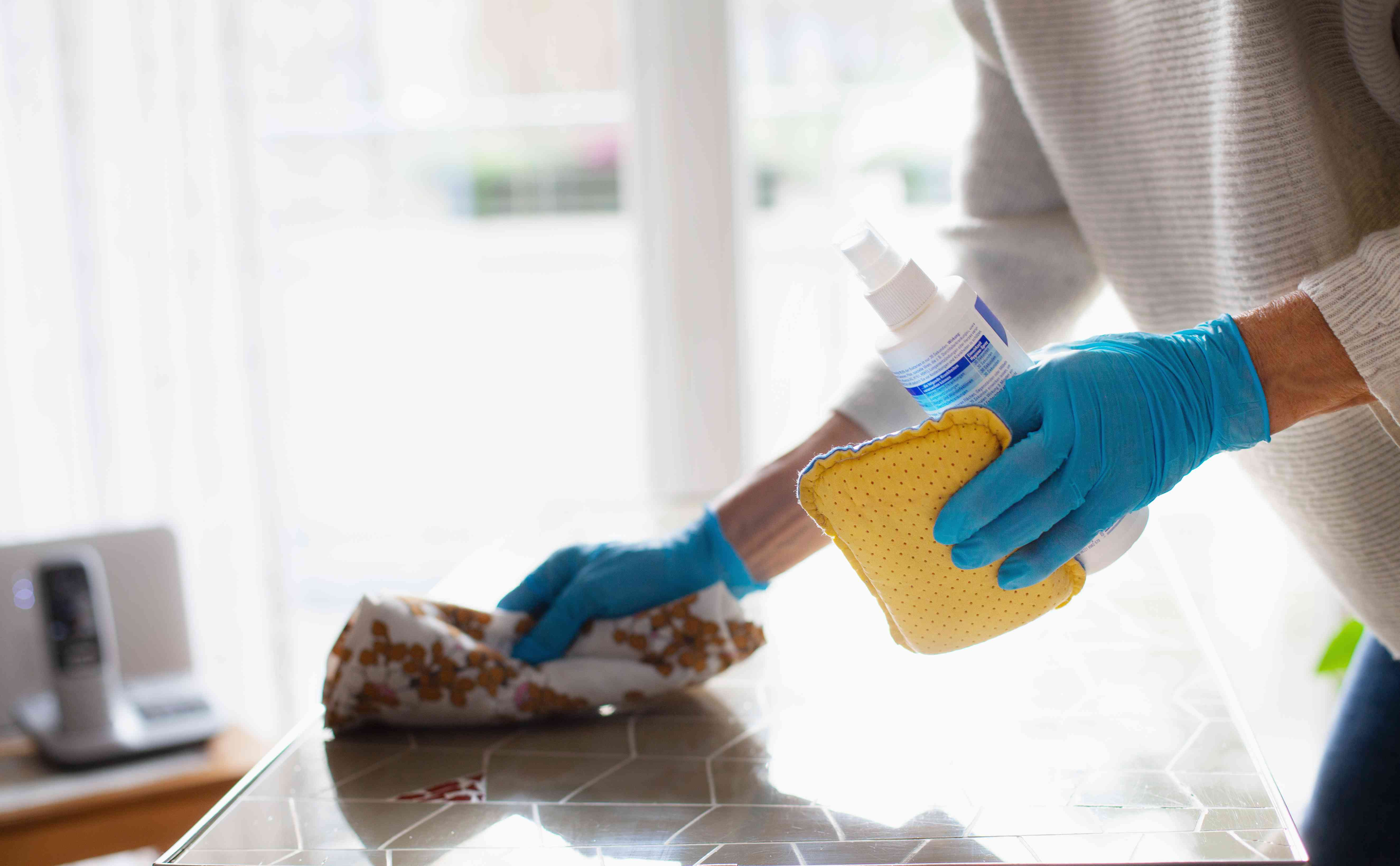 A person wearing rubber gloves and carrying a bottle and sponge wipes a countertop