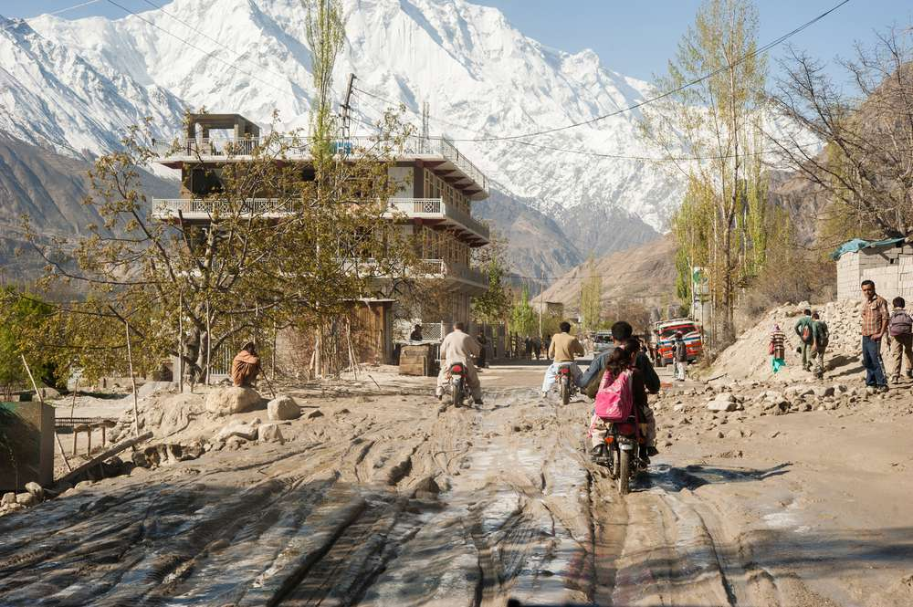 People ride motorcycles on a muddy road in Hunza, Pakistan