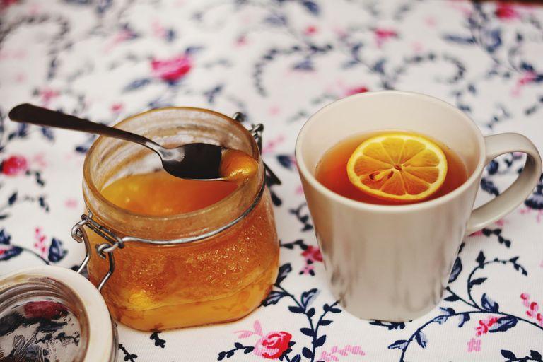 Jar of honey sitting next to a mug of tea with lemon