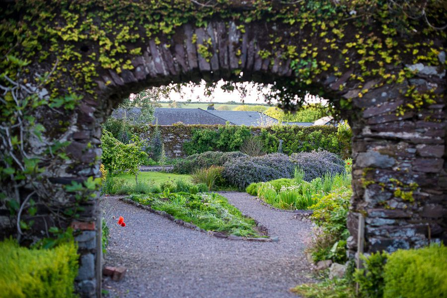 A garden is visible through a stone archway covered with ivy