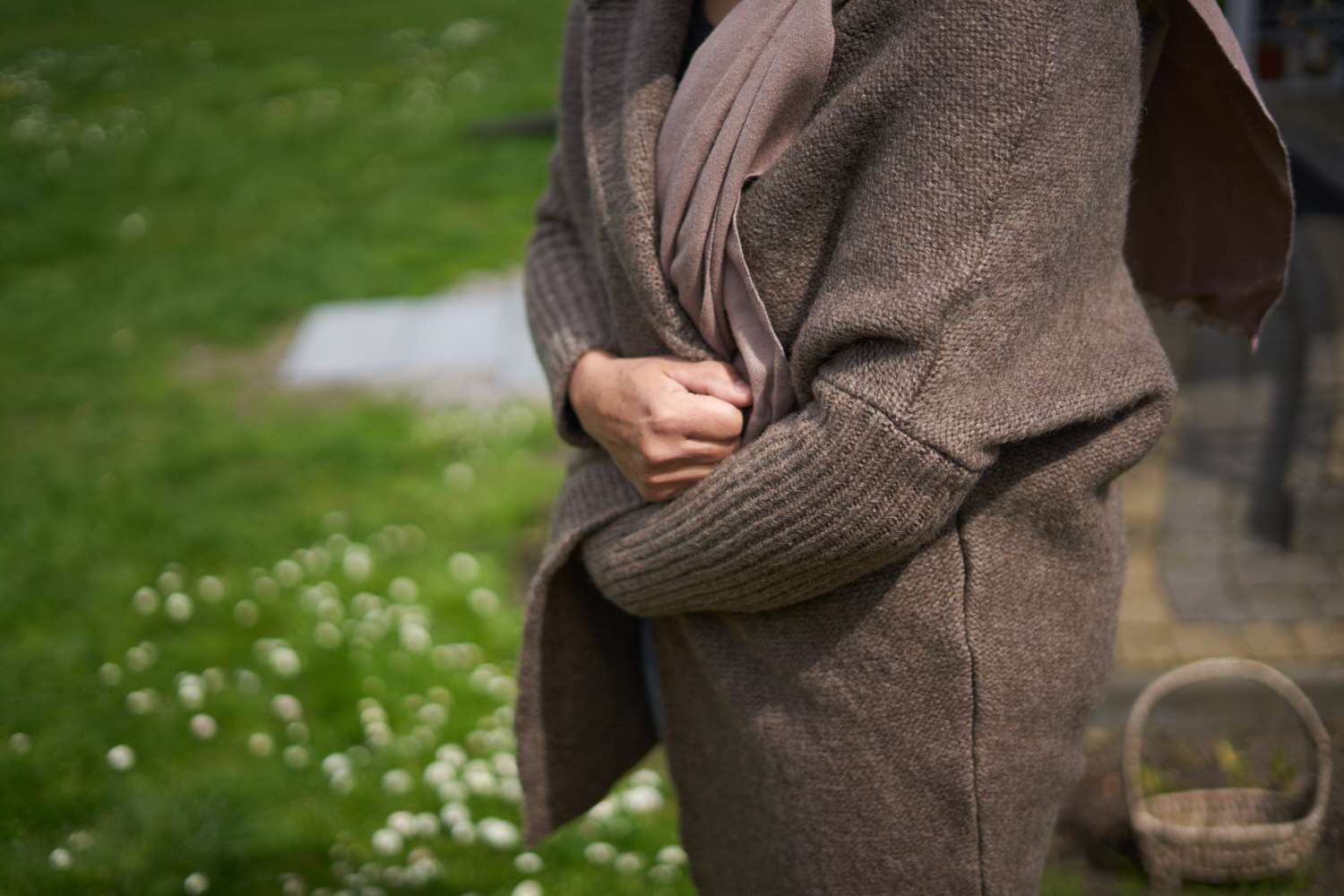 person clutches brown knitted cardigan around them while outside near green grass
