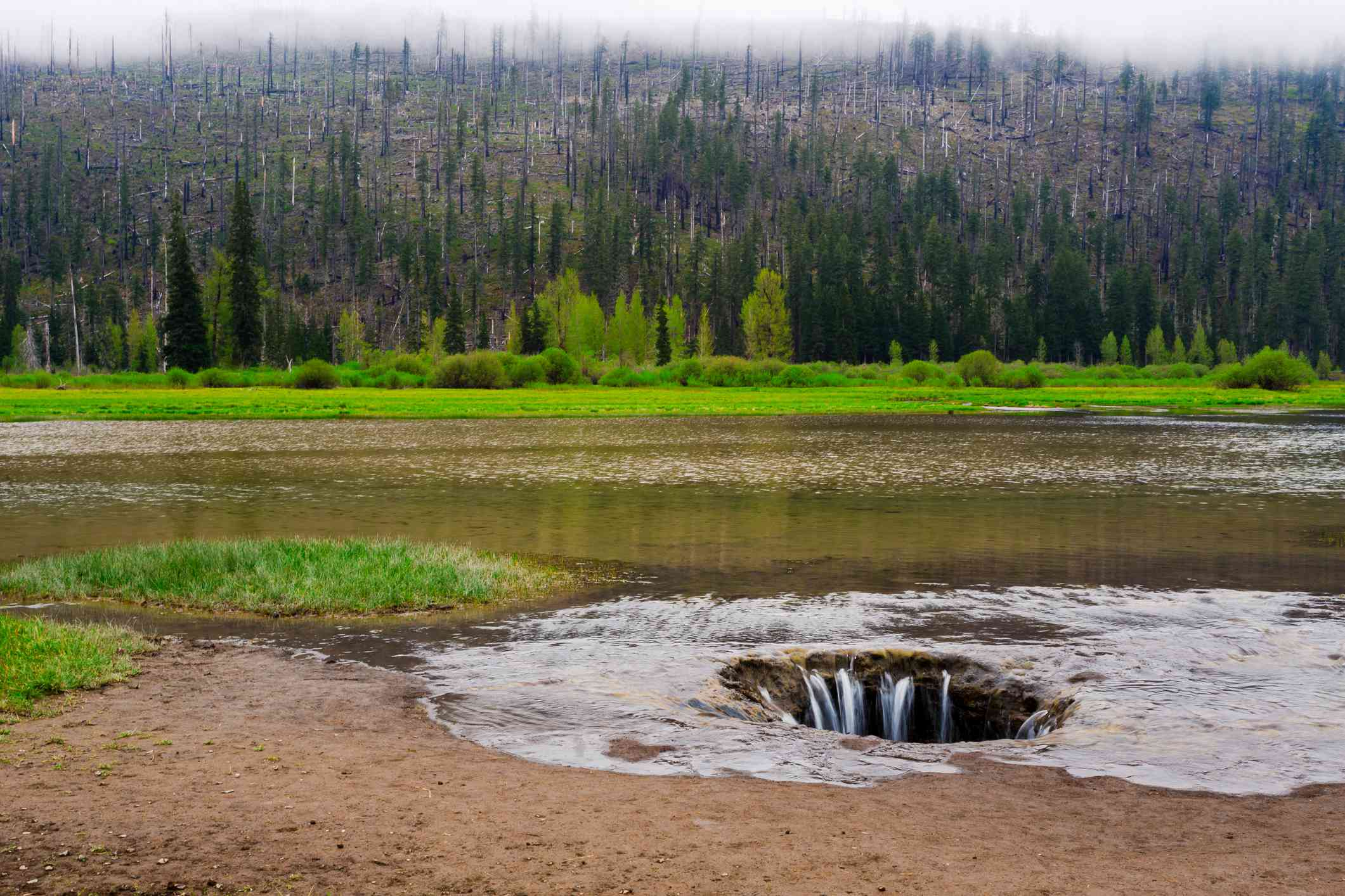 Water in a shallow lake drains into a sinkhole, revealing sandy ground
