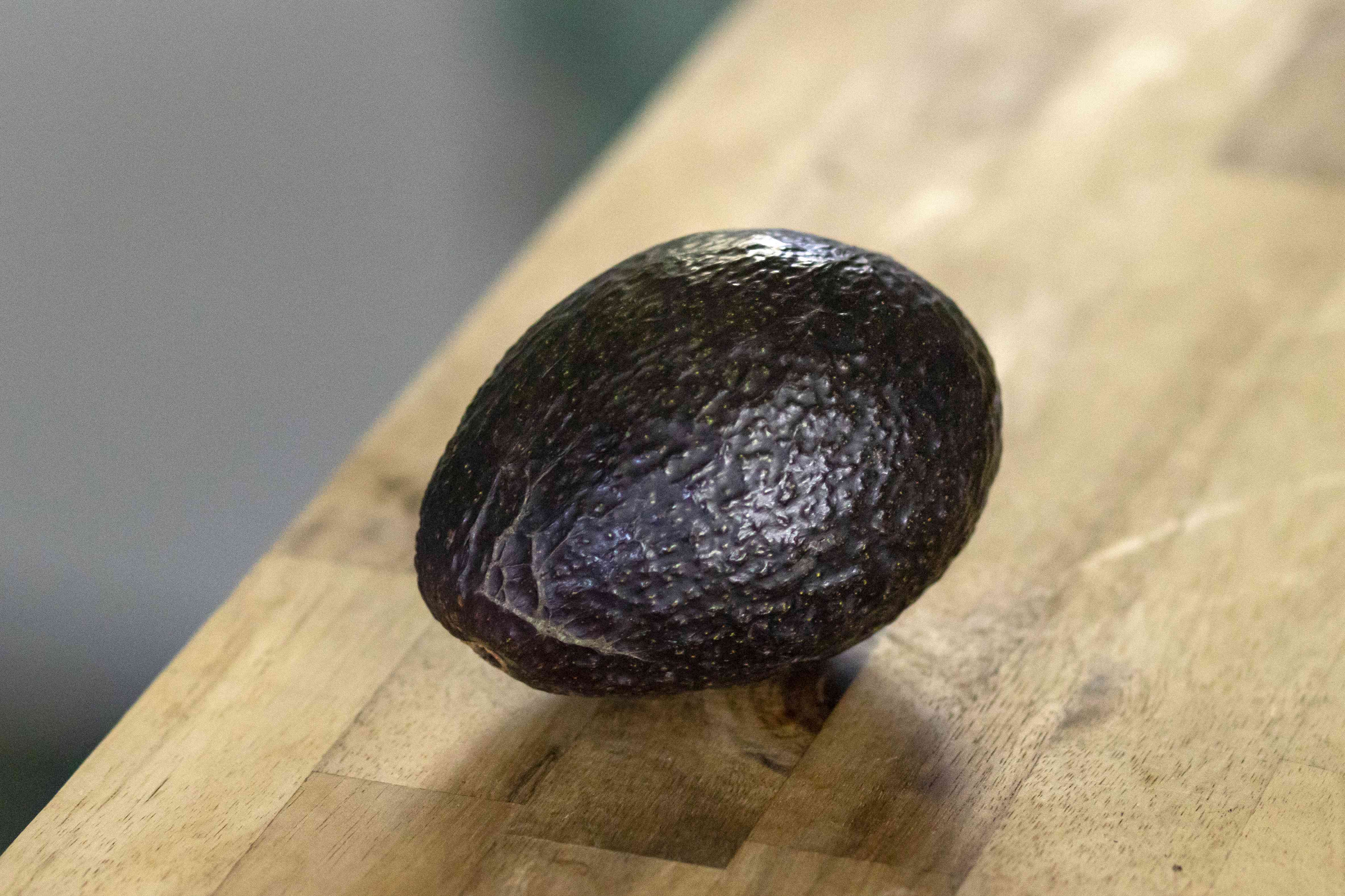one avocado on wooden table