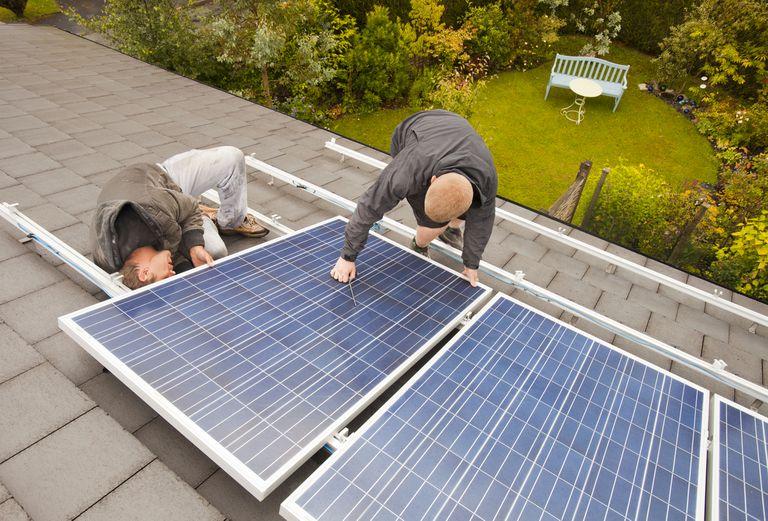 Men install solar panels on a roof.